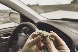 Stock photo of a man smoking marijuana in a vehicle driving a car under the influence of cannabis.